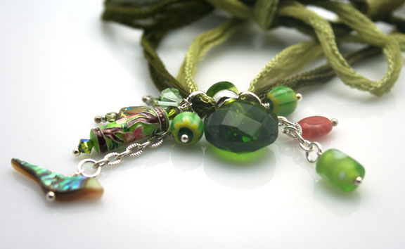 close-up photo of the mini faceted perfume bottle and artistically selected beads on hand-dyed green silk ribbons