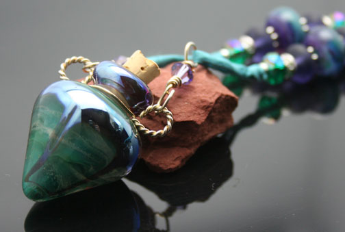 orgeous swirls of teal green, purples, and silver in this aromatherapy bottle necklace