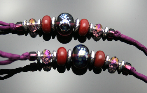 close-up photo of the red and plum custom glass beads