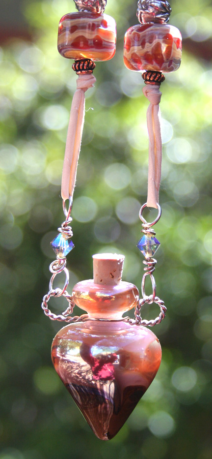 aromatherapy jewelry hanging in the sun to show off the vibrant qualities of the lampwork glass
