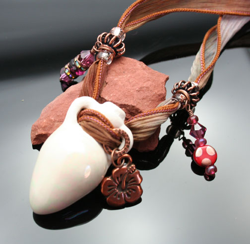 aromatherapy jewelry with a clay amphora pendant, silk ribbon, beads, crystals and charms