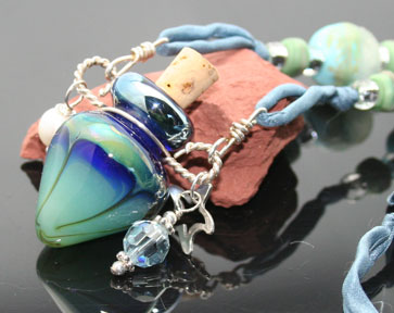 lampwork glass aromatherapy jewelry with silver charms, pearls, beads, and silk